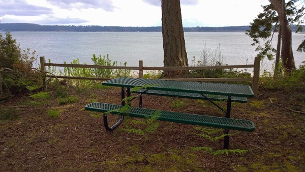 Picnic bench by Puget Sound beach at end of trail around Jacobs Point Park on Anderson Island