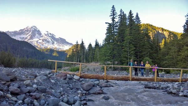 Hikers on log bridge over Nisqually River on Wonderland Trail in Mt Rainier National Park