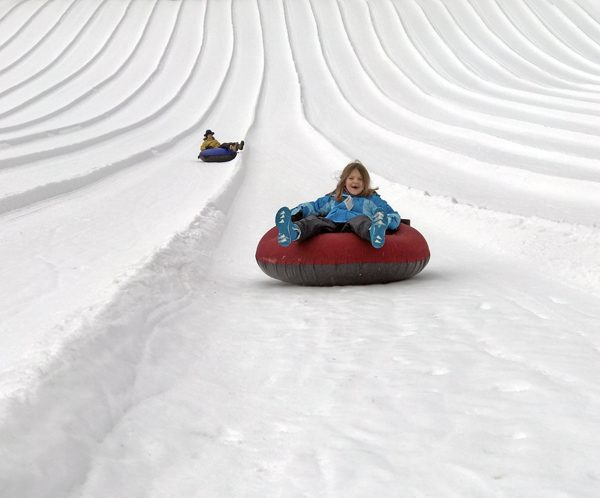 Inner tube riders on snow hill at Snoqualmie Pass Summit Tubing Center