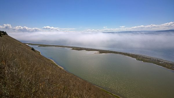 Ebey's Landing Bluff Trail view over Perego's Lagoon and Puget Sound beach with clouds