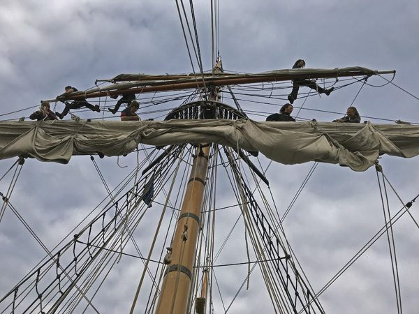 Hawaiian Chieftain crew up mast and rigging in Coupeville Penn Cove